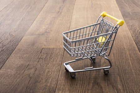 Miniature empty shopping cart on a desktop, grocery shopping and retail concept