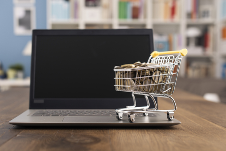 Shopping cart full of money and laptop on a wooden desktop: e-commerce, e-payments and online shopping concept