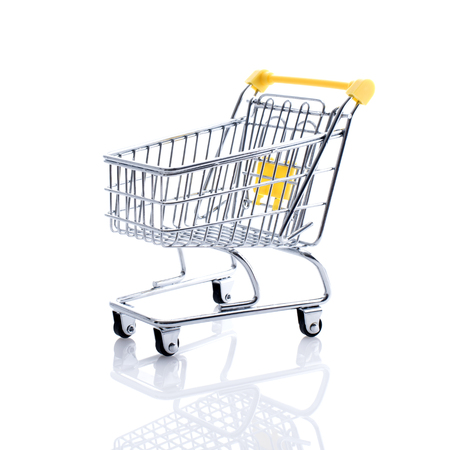 Miniature shopping cart on white background: supermarket grocery shopping and retail concept