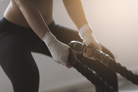 Young sporty woman doing battle rope training, she is swinging the rope, hands close up
