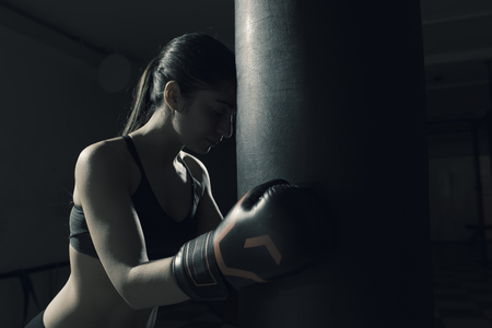 Young pensive woman doing boxing training at the gym, she is wearing boxing gloves and leaning hed head on the punching bag, challenge and determination concept Stock Photo