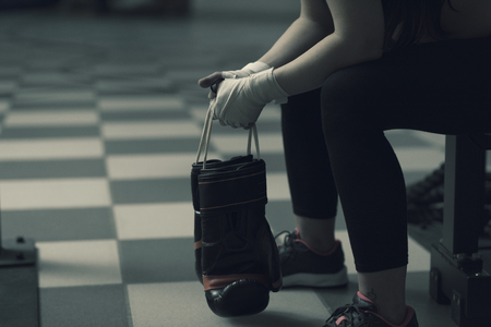 Woman with punching gloves resting on a bench at the boxing club, challenge and focus concept