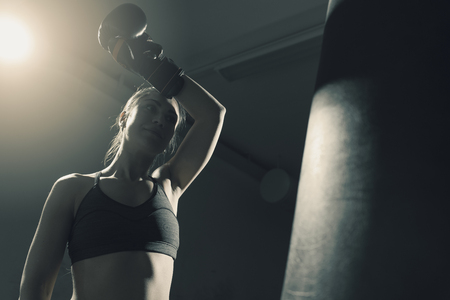 Young woman doing boxing training at the gym, she is wearing punching gloves and smiling