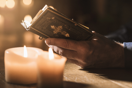 Religious man reading the Holy Bible and praying in the Church with lit candles, religion and faith concept Stock Photo