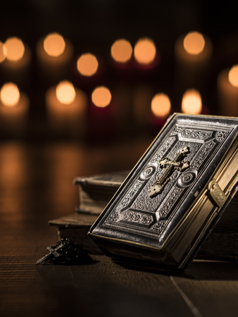 Antique precious Bible, Holy rosary and lit candles in the Church: religion and Christianity concept Editorial