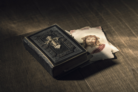 Sacred bible and Holy card with Jesus Christ image on a wooden desk, religion and faith concept