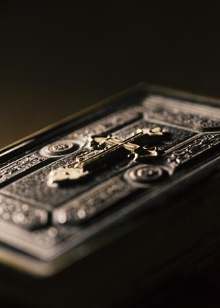 Precious antique Bible with golden cross close up, religion and spirituality concept Stock Photo