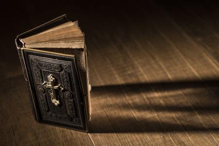 Precious antique Bible on a wooden desktop, religion and spirituality concept Stock Photo
