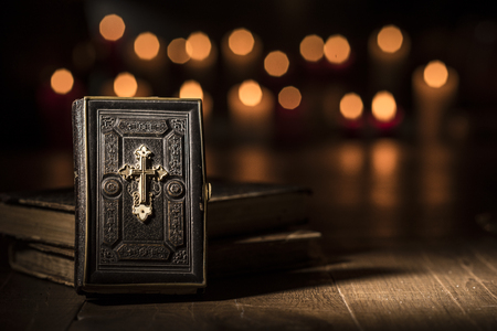 Antique precious Bible and lit candles in the Church: religion and Catholicism concept
