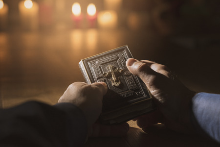 Religious man reading the Holy Bible and praying in the Church with lit candles, religion and faith concept Editorial