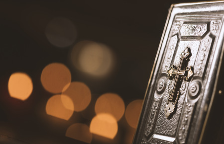 Precious old Bible and lit candles in the Church: Christianity and faith concept