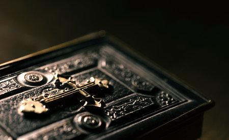 Precious antique Bible with golden cross close up, religion and spirituality concept Editorial