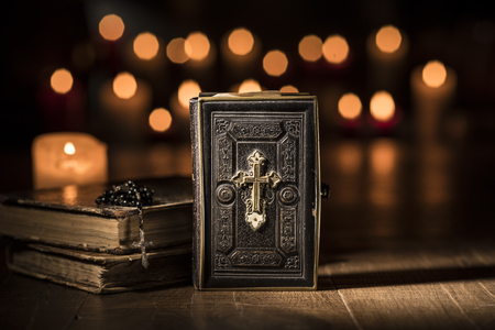 Antique precious Bible, Holy rosary and lit candles in the Church: religion and Christianity concept Stock Photo