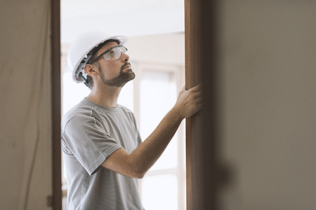 Professional carpenter installing a door jamb, home renovation and carpentry concept