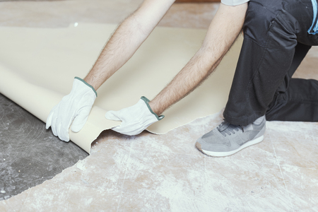 Professional contractor removing an old linoleum flooring: home renovation concept Banco de Imagens