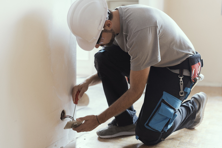 Professional electrician installing sockets using a screwdriver: home renovation and maintenance concept