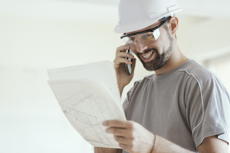 Smiling architect with safety helmet, he is checking a house project and having a phone call