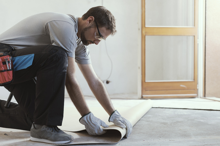 Professional contractor removing an old linoleum flooring: home renovation concept Imagens