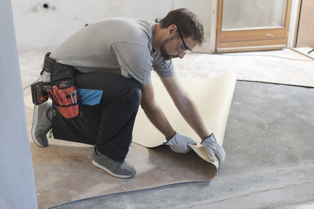 Professional contractor removing an old linoleum flooring: home renovation concept Stock Photo