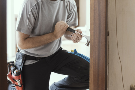 Professional carpenter removing an old door at home: home makeover and renovation concept Stock Photo