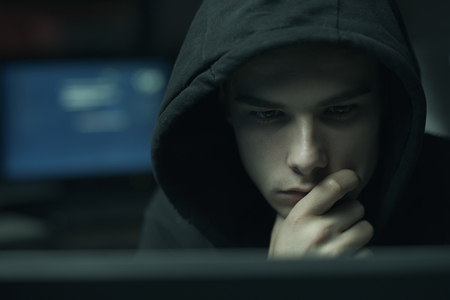 Cool young hacker with hoodie working with computers, cybercrime and data security concept