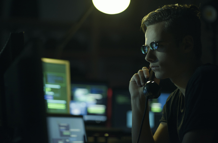 Hacker with sunglasses holding a telephone receiver and computer screens, coding and system hacking concept Stock Photo