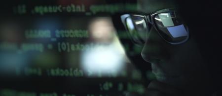 Cool hacker con gafas de sol y código de programación en la pantalla de la computadora, concepto de ciberdelincuencia y piratería