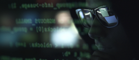 Cool hacker with sunglasses and programming code on the computer screen, cybercrime and hacking concept