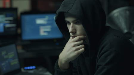 Young hacker with a hoodie thinking with hand on chin and working with computers, technology and cybercrime concept