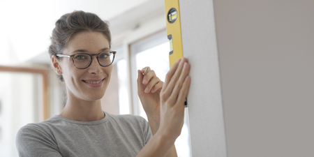 Young woman working with a spirit level and checking the surface of a wall, home renovation and construction concept