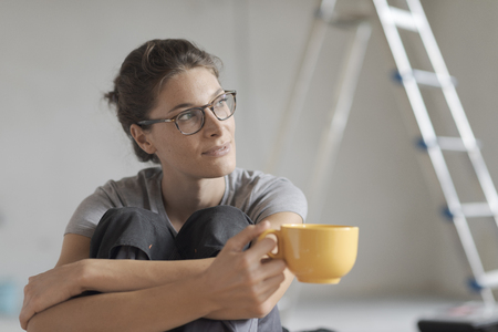 Young smiling woman having a coffee break on the floor and looking away, she is doing a home makeover