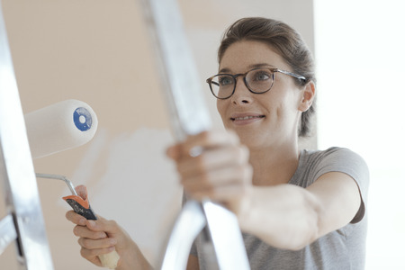 Smiling confident woman painting walls in her new house: home renovation and improvement concept