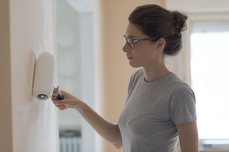 Young woman painting walls at home with a paint roller: home makeover concept Stock Photo - 108157839