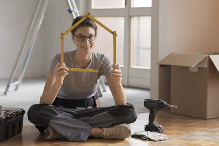 Woman making a house shape with a folding ruler and sitting on the floor, home renovation and construction concept