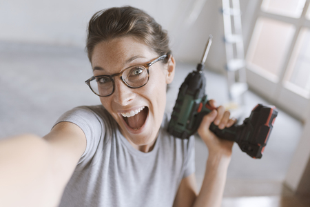 Happy cheerful woman holding a drill and taking a selfie, home renovation and do it yourself concept