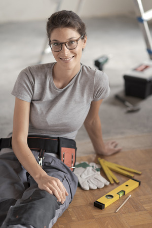 Attractive smiling woman renovating her house, she is sitting on the floor with tools and posing, home makeover concept Stock Photo - 108157846