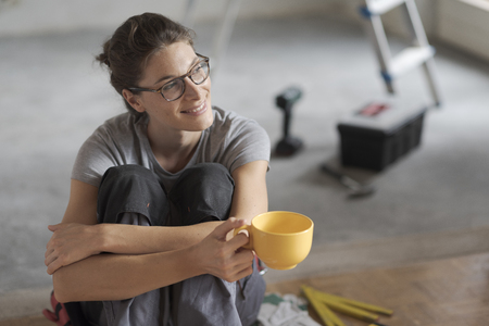 Young smiling woman having a coffee break and sitting on the floor, she is doing a home renovation Stock Photo - 108157852