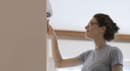 Young woman painting walls at home with a paint roller: home makeover concept