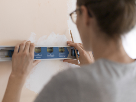 Young woman working with a spirit level and drawing on a wall, home renovation and construction concept Stock Photo - 108157886