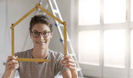 Woman making a house shape with a folding ruler and smiling, home renovation and construction concept Stock Photo - 108157887