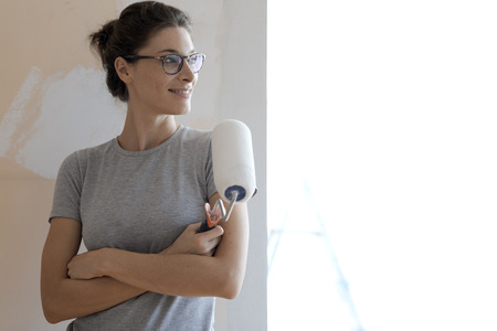 Confident smiling woman posing with a paint roller and looking away: home renovation and redecoration concept