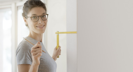 Smiling young woman doing a home makeover, she is measuring a wall using a folding ruler, DIY and house renovation concept 스톡 콘텐츠