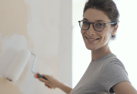 Smiling young woman painting walls in her new house: home renovation and DIY concept