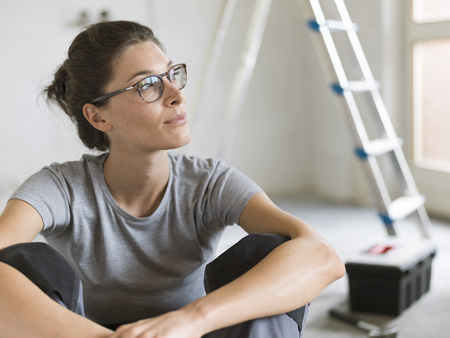 Young woman doing a home renovation in her new apartment, she is sitting on the floor and posing