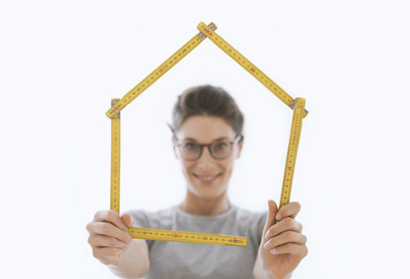 Woman making a house shape with a folding ruler and smiling, home renovation and construction concept