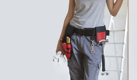 Woman wearing a tool belt and standing, home makeover and DIY concept Stock Photo