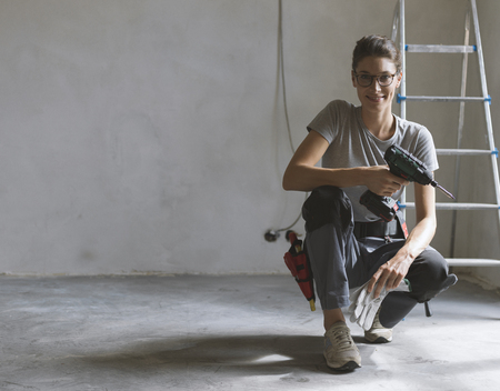 Professional repairwoman with tool belt doing a home renovation, she is posing and holding a drill Stock Photo - 108157902