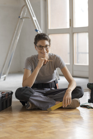 Attractive smiling woman working on a home renovation, she is sitting on the floor with tools and posing, house renovation concept