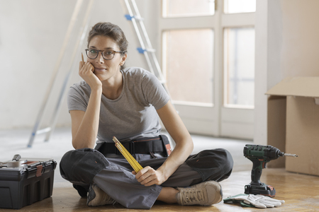 Young woman moving in her new house and doing a home makeover, she is sitting on the floor with tools and cardboard boxes Stock Photo