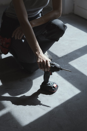 Woman taking a drill from the floor: DIY and home renovation concept